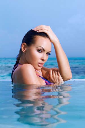 Beautiful woman resting in pool at Maldives photo