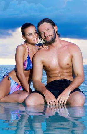 Romantic couple sitting next to swimming pool Stock Photo - 6879026