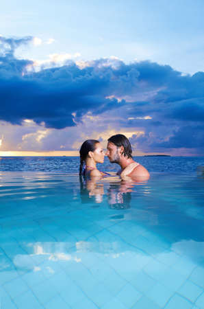 romantic kiss: Romantic couple alone in infinity swimming pool