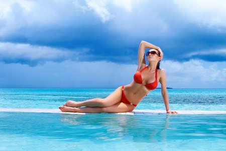 아름 다운 여자 몰디브에서 수영장 근처 휴식