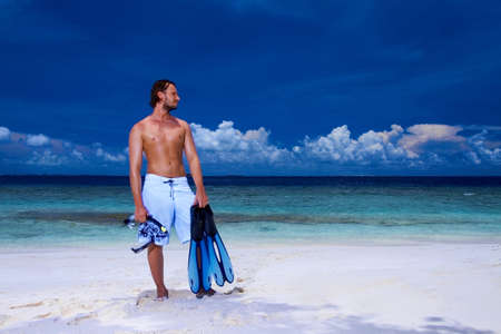 snorkling: Handsome man is standing on the beach holding fin