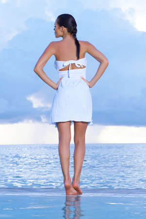 Beautiful woman standing near pool at Maldives photo