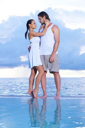 Romantic couple sitting next to swimming pool Stock Photo - 7027185