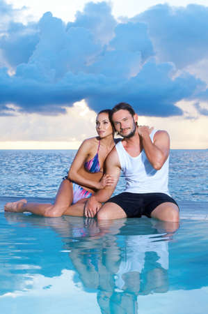 Romantic couple sitting next to swimming pool Stock Photo - 7027181