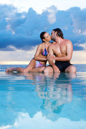 Romantic couple sitting next to swimming pool Stock Photo