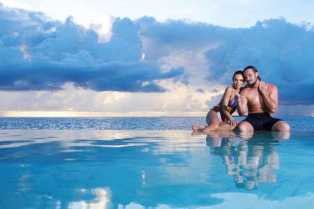 bikini couple: Romantic couple sitting next to swimming pool Stock Photo