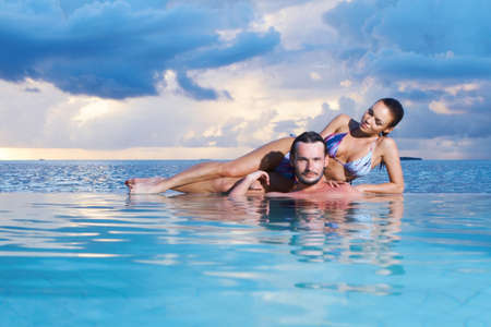 Romantic couple alone in infinity swimming pool photo