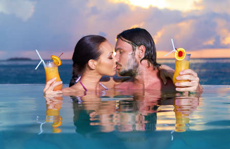 Romantic couple alone in infinity swimming pool Stock Photo - 7027218