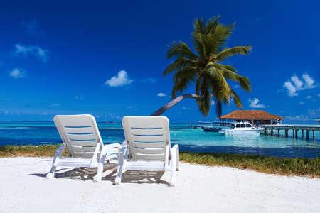 bahamas: Twee ligbedden op het strand op de Malediven  Redactioneel