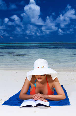 Beautiful woman reading book near water at Maldives photo
