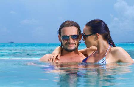 Romantic couple alone in infinity swimming pool Stock Photo - 7027172
