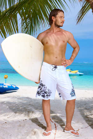 Handsome man standing with surfing board on the beach photo