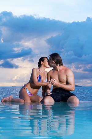 Romantic couple sitting next to swimming pool photo