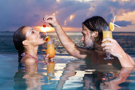 Romantic couple alone in infinity swimming pool photo