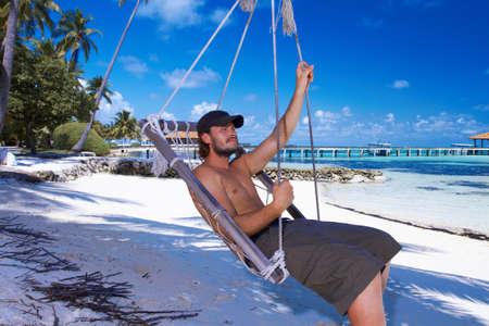 Handsome man resting near water at Maldives photo