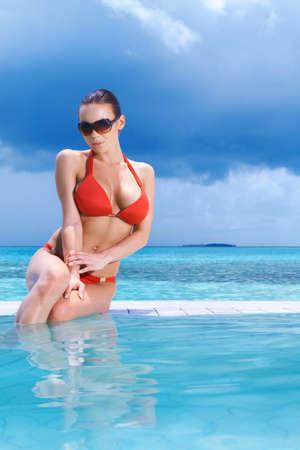 Beautiful woman resting near pool at Maldives photo
