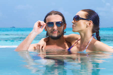 Romantic couple alone in infinity swimming pool Stock Photo - 7157859