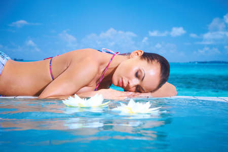 Beautiful woman resting near pool at Maldives photo