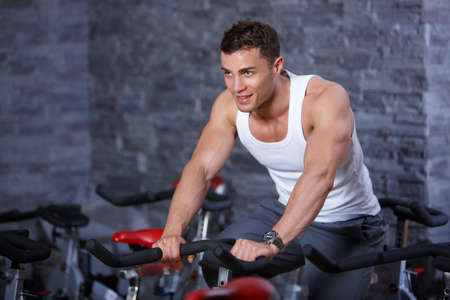 Handsome man at the gym doing exercises photo