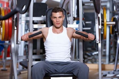 gym equipment: Handsome man at the gym doing exercises