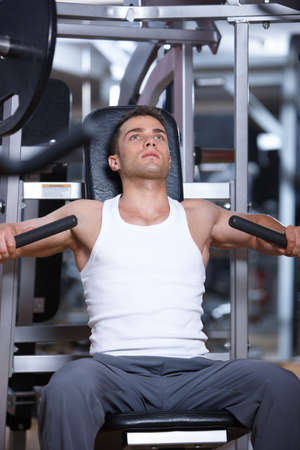 weight machine: Handsome man at the gym doing exercises