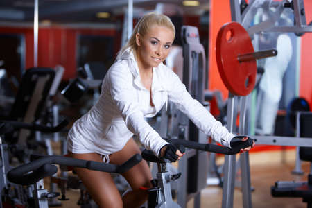 exercise machine: Beautiful woman exercising at the gym Stock Photo