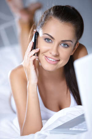 Beautiful woman working on laptop on white bed photo