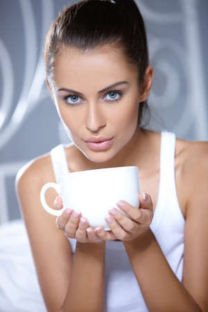 coffee houses: Beautiful woman holding cup on white bed Stock Photo