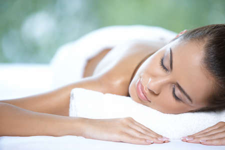 massage therapy: Beautiful woman is resting on spa bed