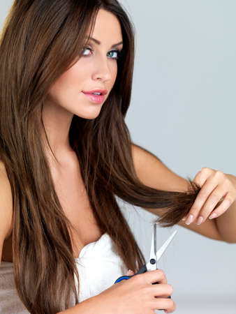 Beautiful woman cutting her hair tips with scissors photo
