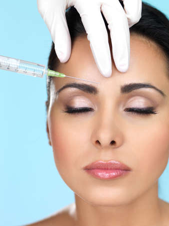 injection: Beautiful woman gets botox injection in her face