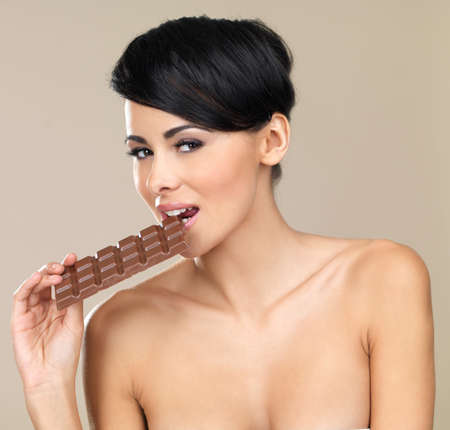 Portrait of beautiful woman, she holding chocolate bar photo