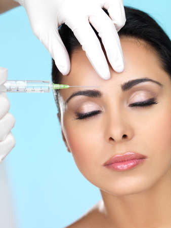 botox: Beautiful woman gets botox injection in her face