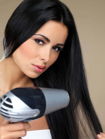 Portrait of beautiful woman, she holding hair dryer photo