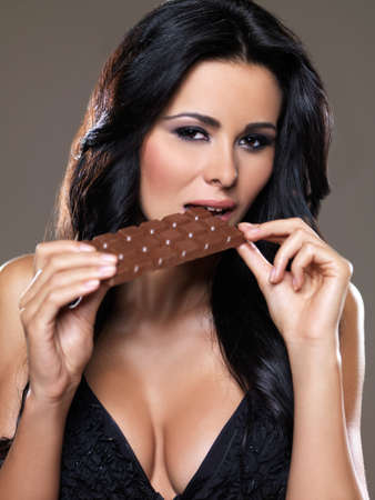 Portrait of sexy woman, she holding chocolate bar photo