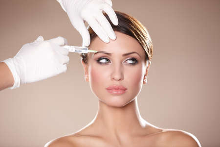 medical injection: Beautiful woman gets botox injection in her face