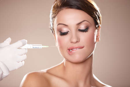 syringe injection: Beautiful woman gets botox injection in her face