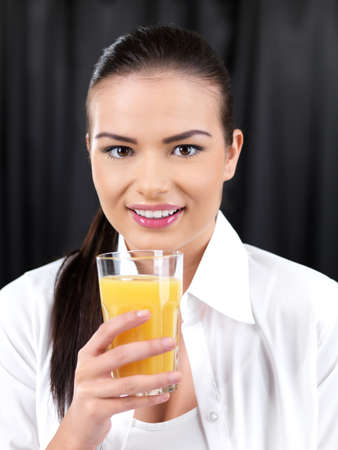 Portrait of beautiful woman, she holding glass of orange juice photo