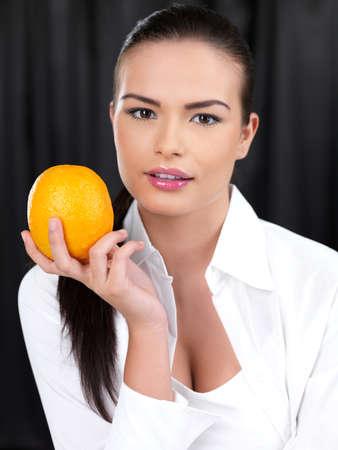 Portrait of beautiful woman, she holding orange fruit photo