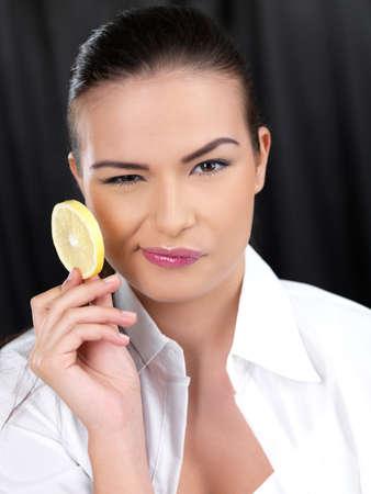 Portrait of beautiful woman, she holding lemon slice photo