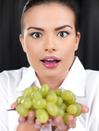 Portrait of beautiful woman she holding green grapes photo