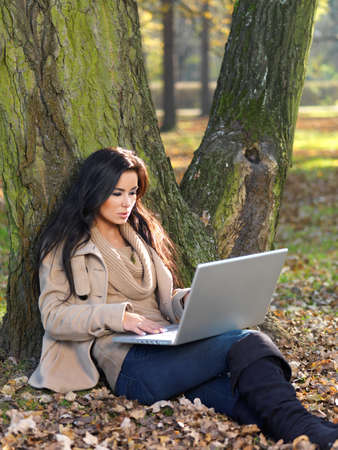 Beautiful woman working on laptop in park during autumn season photo