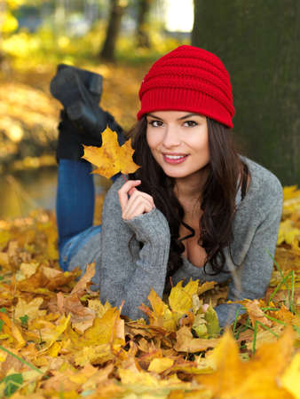 lying in leaves: Beautiful woman spending time in park during autumn season