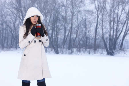 Beautiful woman holding thermal mug in snowy winter outdoors photo