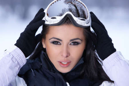Beautiful woman wearing goggles in snowy winter outdoors photo