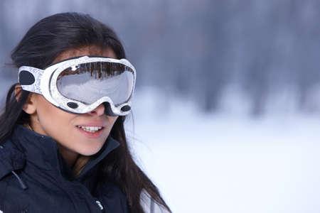 ski goggles: Beautiful woman wearing goggles in snowy winter outdoors