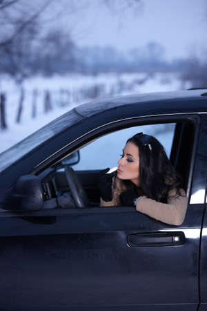 Beautiful woman in car in snowy winter outdoors photo
