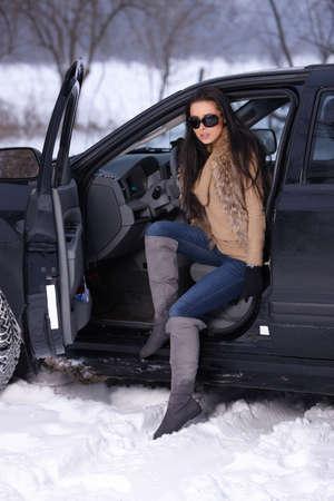 Beautiful woman in car in snowy winter outdoors photo
