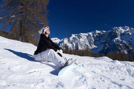 Girl with snowboard is sitting on snow photo
