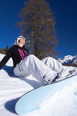 sunbath: Cute Gril met snowboard neemt zonnen op sneeuw Stockfoto